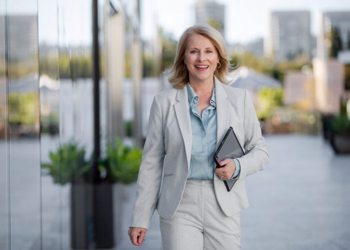 Mature successful business woman walking to corporate job, cheerful with confidence, skyline in background